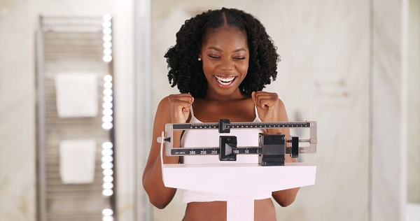 Woman happy while she stands on a scale and sees weight loss