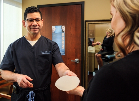 Dr. Victor Perez and patient discussing breast implants