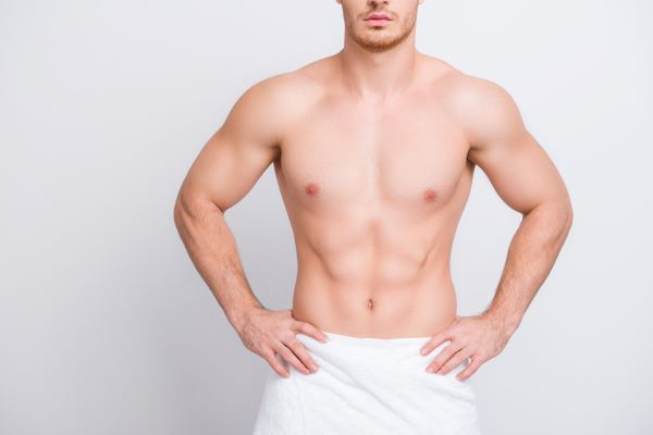 A man with a bare chest and towel stands with his hands on his hips and a straight face