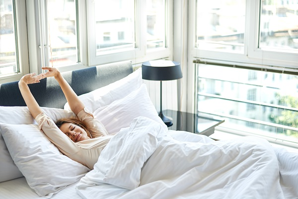 Woman relaxing in bed during breast augmentation recovery
