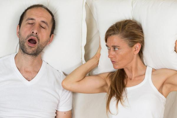 couple in bed- woman covering her head with pillow to drown out man snoring