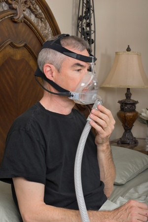 man adjust CPAP mask before going to bed
