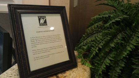 our Client Satisfaction promise in a wooden frame at the front desk