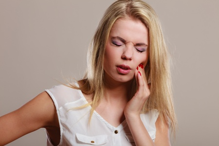 woman with toothache pain holding her cheek