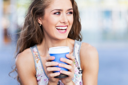 Woman with porcelain veneers smiling, holding a coffee cup