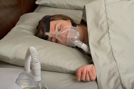 woman lying in bed wearing CPAP mask