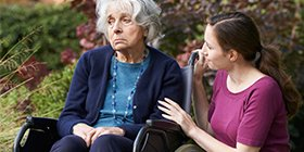 Young woman comforting an elderly woman in a wheelchair who has been subjected to abuse at her nursing home