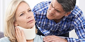 Man comforting a woman in a neck brace who was injured due to someone else's negligence