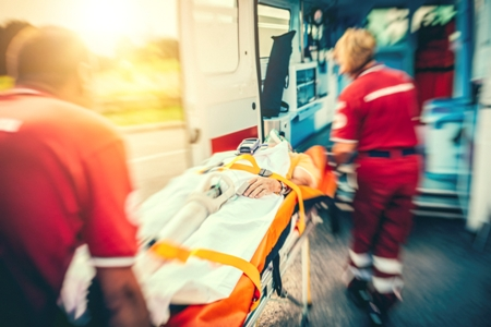 paramedics load accident victim into ambulance