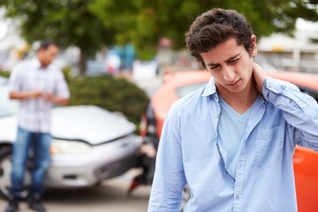 young man rubs his neck after a car accident