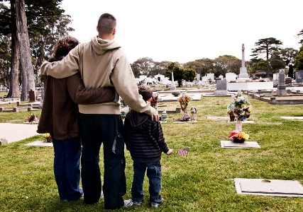 mom, dad and son visiting grave site