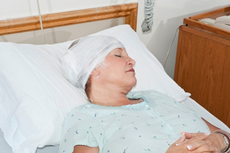 woman with bandaged head lying in hospital bed